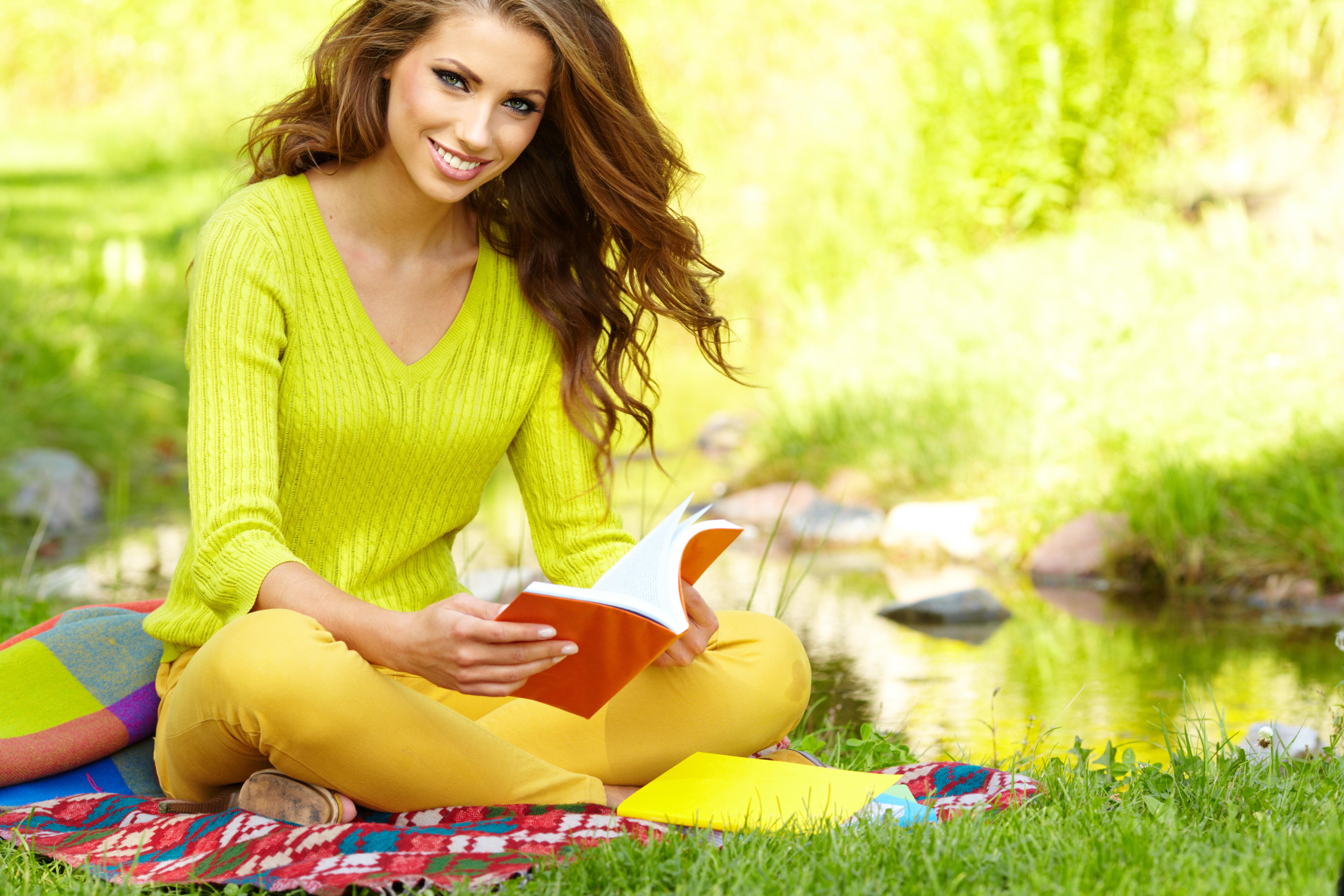 Девушка с книгой на траве бесплатно